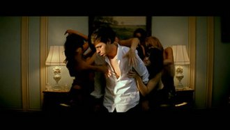 Tonight (I'm Lovin' You) - Iglesias on the bed with several women behind him.