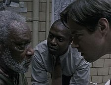 Two men lean in closely while speaking with a bearded, unhappy-looking man inside a police interrogation room.