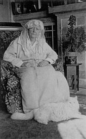 A monochrome portrait photograph of an elderly woman sitting in her home with a white Persian cat resting at her feet. The woman is wearing a light-colored dressing gown, her closed hands on her lap, her head tilting to one side, looking tight-lipped at the photographer, a white lace veil and scarf over her hair and framing her face.