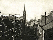 St Pancras clocktower rises above tenement blocks in King's Cross in the 1980s. Etching by Colin Bailey