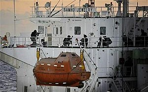 A chemical tanker with South Korean naval personnel in full combat gear onboard; the tanker shows signs of a fight with broken glass and holes in the windows.
