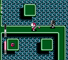 A person in a suit is on a green bridge over water. A robot is shooting at this person from the right. There is a red power-up item on an island next to the bridge.
