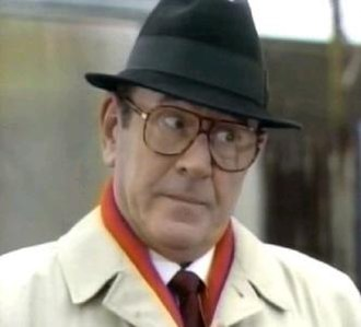 Frank Butcher - Frank in the early 1990s. The character was often seen wearing a trilby, raincoat and large tinted glasses.