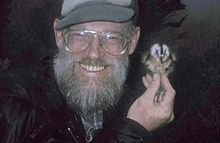 A smiling, bearded man holds a small bird near his left ear with his right hand.