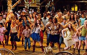 "Hoedown Throwdown - Cyrus (center) performing ""Hoedown Throwdown"" in its music video, an excerpt from Hannah Montana: The Movie."