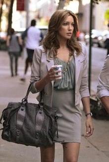 A tall blonde woman carrying a metallic handbag and a coffee cup walks next to an individual wearing a white shirt