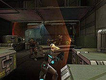 A young blonde woman in an armored suit and carrying a gun runs for cover behind crates while a group of guards take aim, using a sensor device to sweep the area.