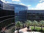 A modern építészeti stílusú épületet fém és üveg borítja a fák és a kék ég hátterében.