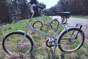 A white bicycle parked in the grass.