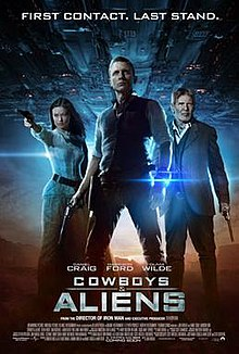 "A man wearing a metal bracelet glowing a blue light on his left wrist, with a revolver in his right hand. To the left, a woman aiming a revolver. To the right, an older man wielding a revolver. In the background, a large metal object over a desert landscape. Above is shown ""FIRST CONTACT. LAST STAND."" Below them are the names of Daniel Craig, Harrison Ford, and Olivia Wilde above the title ""COWBOYS & ALIENS"", film credits, and theatrical release date."