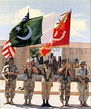 A Piffer infantryman (centre) in Somalia, with the green flag of Pakistan.