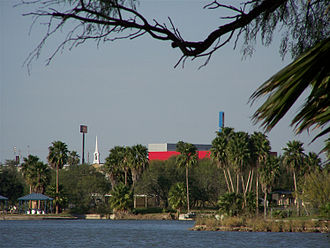 "La Joya Independent School District - Picture taken from one of La Joya's lakes, with the red, grey, and black Alejandro ""Alex"" H. Saenz Performing Arts Center in the background, along with the white steeple of the Church of Jesus Christ of Latter-day Saints."