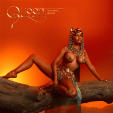 Minaj posing on a fallen tree trunk in front of a setting sun, wearing pasties and Egyptian head beads.