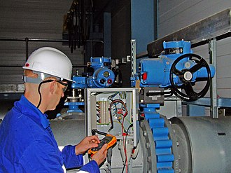 Valve actuator - Electric actuator (blue cylinder) on a valve in a power plant. A black handwheel is visible on the actuator, which allows manual positioning of the valve.  The blue valve body is visible in-line with the pipe. The valve actuator opens or closes the butterfly disc of the valve based on electrical signals sent to the actuator.  Another valve actuator is visible in the background, with windows to indicate the valve position.