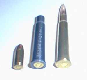 Caliber conversion sleeve - A 32 ACP FMJ cartridge, a 32 ACP FMJ cartridge in a blued .303 British supplemental chamber, and a .303 British 180gr FMJ cartridge (left to right)