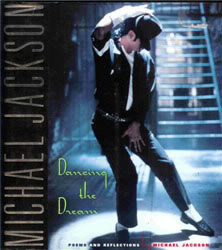 Front cover of book showing a man under a spotlight in front of metal stairs. He wears black trousers, a black shirt and a black fedora. Under his shirt is a white T shirt, which matches the color of his socks, right armband and right arm brace. The man is striking a pose: legs apart and to the left, he looks down to the ground, as his braced right hand holds his hat atop his head. His left hand covers his crotch.