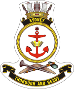 "A ship's badge. A naval crown sits on top of a black scroll with ""SYDNEY"" written in gold. This is atop a yellow, rope-patterned ring, in which a red anchor is centred. Below the ring are a stone axe and a nulla nulla sitting on top of a boomerang. At the bottom of the badge is a black scroll with ""THOROUGH AND READY"" written."