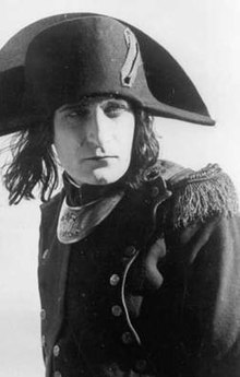 A monochrome photographic portrait of a handsome man in his late 20s wearing a French general's uniform from the 1790s and a cocked hat over stringy dark hair that reaches his shoulders
