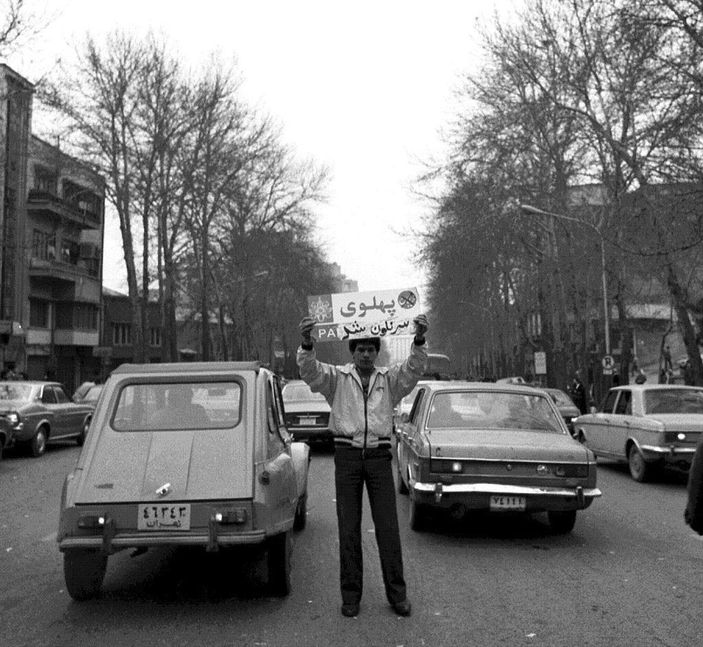 در تصویر، جوانی انقلابی پلاک خیابان پهلوی را کنده و عبارت «سرنگون شد» را به صورت دستنویس به پایین پلاک خیابان پهلوی اضافه کردهاست.