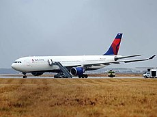 A large white jet with a red-and-blue tail on a runway amid a yellowed field of grass. A gray truck has extended a ladder to the plane's door.