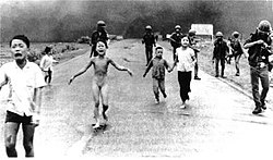 Group of children and soldiers moving on foot away from a distant cloud of smoke rising from the ground. Several children are crying and one in the center is also naked as she runs toward the camera.