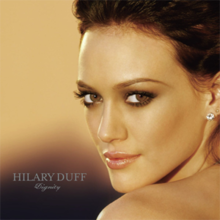 "The face and shoulders of a young woman looking over her left shoulder. She has brown hair and wears small crystal earrings. To the left of her image, the words ""Hilary Duff"" are written in silver, capital letters, with ""Dignity"" in silver, italic, cursive letters below that."