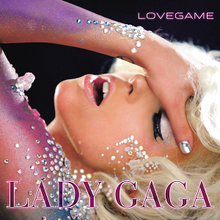Gaga places her left hand on her forehead and tilts it backwards. The arm is painted in blue and violet colors and glitters are pasted on it.
