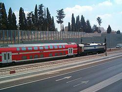 רכבת נוסעים דו-קומתית בדרכה מתחנת הרכבת כפר סבא לתחנת הרכבת הוד השרון חולפת בין נתיבי הכביש, על רקע הקירות האקוסטיים התוחמים את ציר התנועה