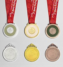 Six medals are shown to display the front and back of each. From left to right, silver, gold and bronze.