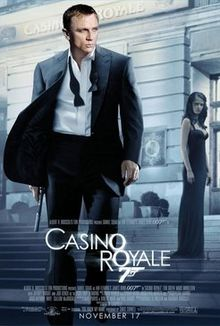 "A man in a business suit with a loose tie holding a gun. Behind him is a building with a sign reading ""Casino Royale"", and a woman in a black dress who stands on the entrance staircase. At the bottom of the image is the title ""Casino Royale"" – both ""O""s stand above each other, and below them is a 7 with a trigger and gun barrel – and the credits."