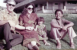A young boy (preteen), a younger girl (toddler), a woman (about age thirty) and a man (in his mid-fifties) sit on a lawn wearing contemporary c.-1970 attire. The adults wear sunglasses and the boy wears sandals.