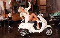 Picture of a white Vespa scooter standing in a street corner. A blonde woman is sitting on the scooter. She is wearing a white short dress and white-heeled shoes. Her bare right leg is put up on the handle of the Vespa. Behind her, on the left, the bonnet of a indigo colored car is visible, while the bowed down head of a man wearing a white hat is visible on her right