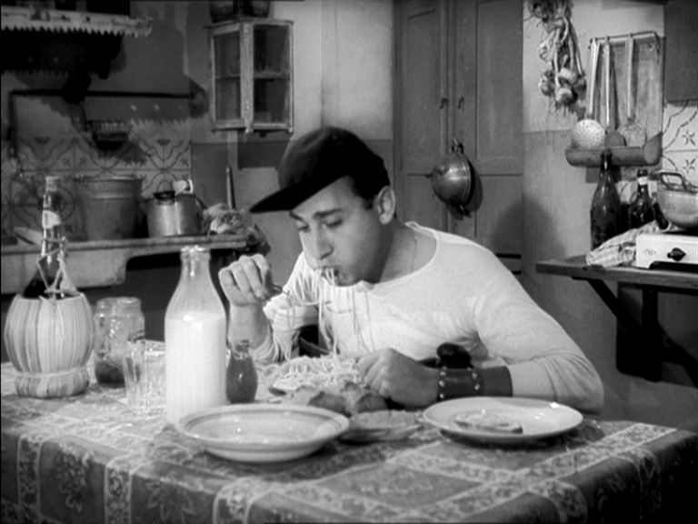 Un Americano a Roma (1954). Alberto Sordi representing what became an Italian post-war stereotype: pasta, Chianti and a busy kitchen, giving a wink to American culture (Sordi is eating spaghetti wearing a baseball cap)