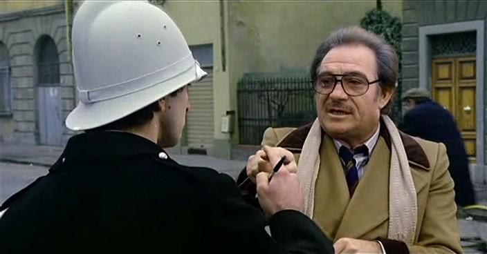 Un fotogramma di Amici miei (1975) di Mario Monicelli. In questa sequenza il conte Mascetti (Ugo Tognazzi) usa la supercazzola con il vigile (Mario Scarpetta)