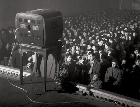 Un apparecchio televisivo montato davanti allo schermo consentiva, negli anni cinquanta, in Italia, agli spettatori di un cinematografo di assistere, prima della proiezione del film, al programma di successo