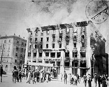 A black and white photograph of a burning building, with a small crowd watching.