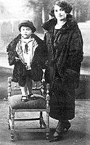 Un bambino in piedi su di una sedia accanto alla madre.