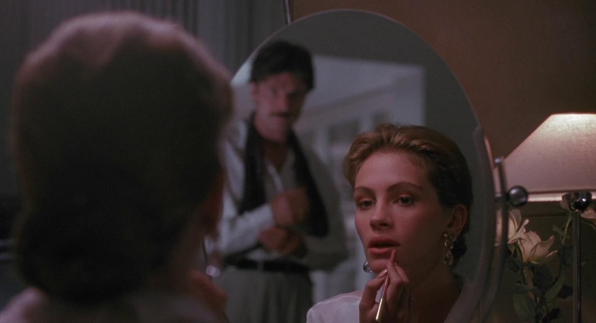 Julia Roberts si mette il rossetto in una scena del film A Letto con il Nemico, 1991.