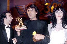 Cutugno (al centro) viene premiato al XXX Festival di Sanremo dai conduttori Roberto Benigni e Olimpia Carlisi