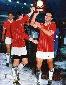 Cabrini (a destra), con i compagni di squadra Tardelli e Brio — e con indosso le maglie degli avversari del Liverpool —, mostra ai tifosi la targa della Supercoppa UEFA 1984 vinta con la Juventus.