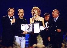 Gabriella Carlucci (al centro) conduttrice del Festival di Sanremo 1990 con Johnny Dorelli (primo da sinistra), mentre premiano Marco Masini (secondo da sinistra).
