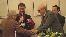 Eisner, a destra, stringe la mano a Giovan Battista Carpi, dietro di loro Gianfranco Goria e Luca Boschi - Lucca 1998