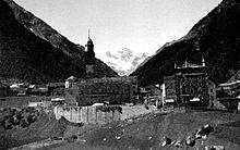 Immagine di Cogne nel 1915. A sinistra è visibile la parrocchiale, mentre l'edificio a destra era la residenza reale di Vittorio Emanuele II durante le sue permanenze in paese nei periodi di caccia.