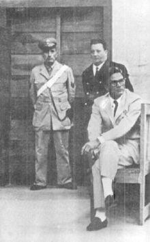 Pasolini seduto, alle sue spalle un carabiniere e un cancelliere del tribunale.