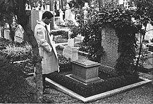Un uomo in contemplazione davanti a una lapide di un cimitero.