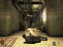 A video game screenshot of a man leaning on the floor while holding a gun in each hand and firing them at another man down a hallway.