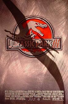 Movie poster with a logo at center of a skeleton of a Spinosaurus, with its mouth agape and hands lifted up. The background of the logo is red, and right below it is the film's title. A shadow covers a large portion of the movie poster in the shape of a flying Pteranodon. At the bottom of the image are the credits and release date.
