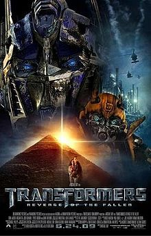 The human-like faces of two robots stand atop a pyramid. A helicopter flies over an industrial facility on the right side of the image, and a young couple is seen in front of the pyramid. The film title and credits are on the bottom of the poster.