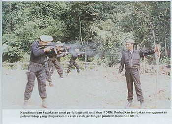 Anggota Komando 69 semasa menjalani latihan menembak HK MP5 di lapang sasar. Perhatikan salah seorang anggota unit ini cuba menembak melepasi celah jari jurulatih ke papan sasaran dengan menggunakan peluru hidup. Latihan sebegini amatlah menguji kemampuan seseorang penembak terutamanya menembak ke arah sasaran yang sukar, lebih-lebih lagi sekiranya berhadapan dengan pihak musuh yang menggunakan tebusan.