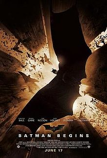 A man in a batsuit spreads his wings while looking down. Tall skyscrapers extend above, and bats fly around him.